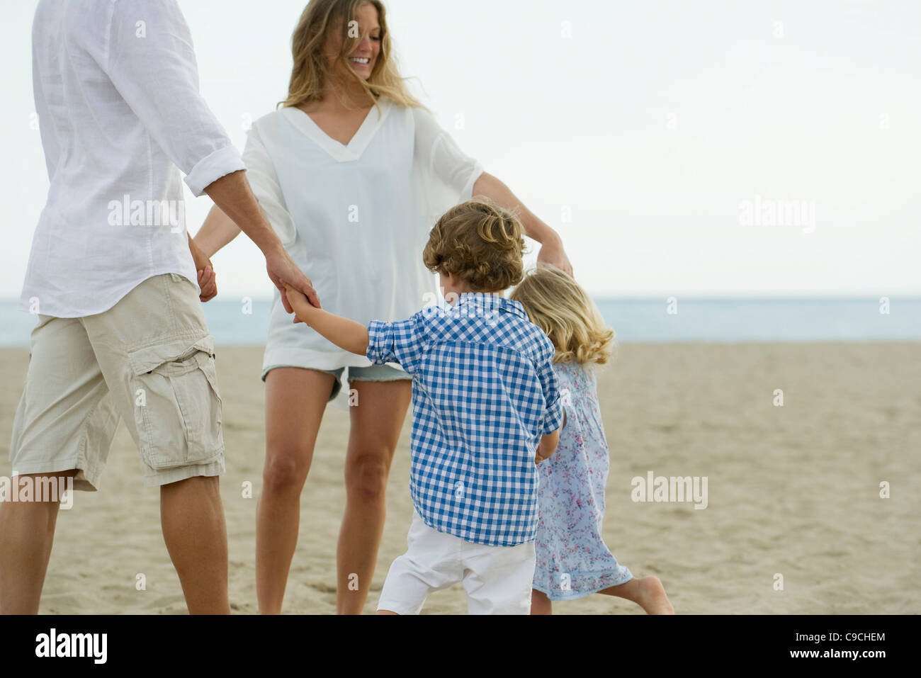Family playing ring-around-the-rosy at the beach - Stock Image