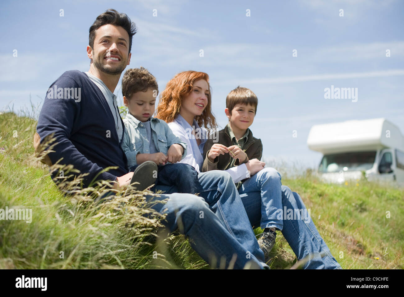 Parents and young boys sitting on meadow - Stock Image