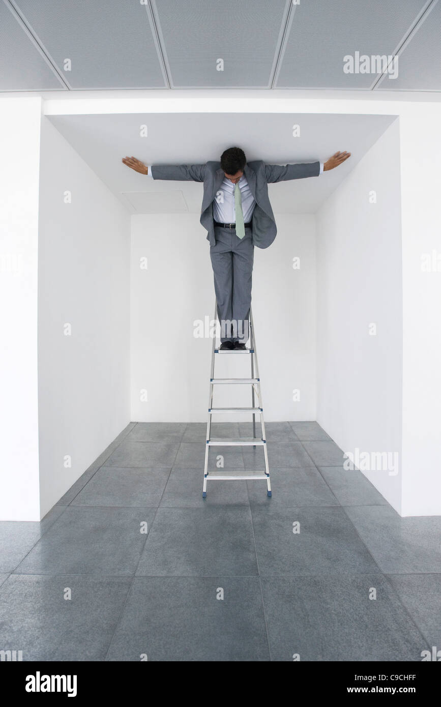 Executive standing on stepladder, arms outstretched on ceiling - Stock Image