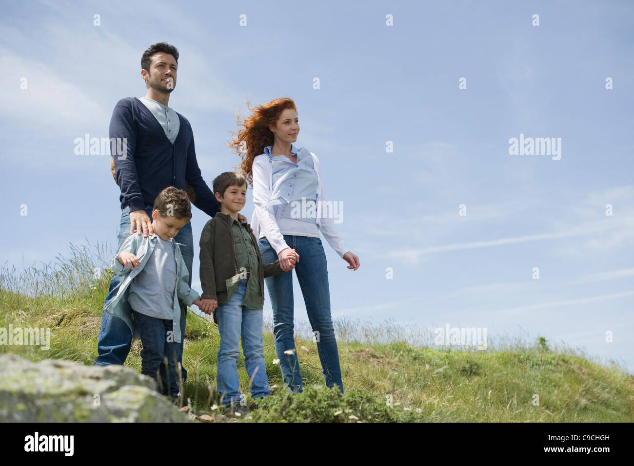 Parents and young boys standing on meadow, portrait - Stock Image