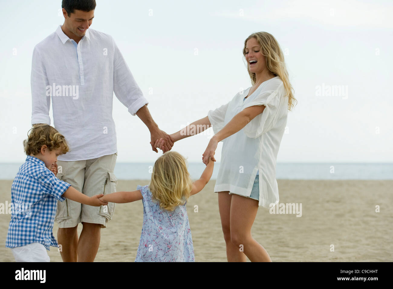 Family holding hands at the beach - Stock Image