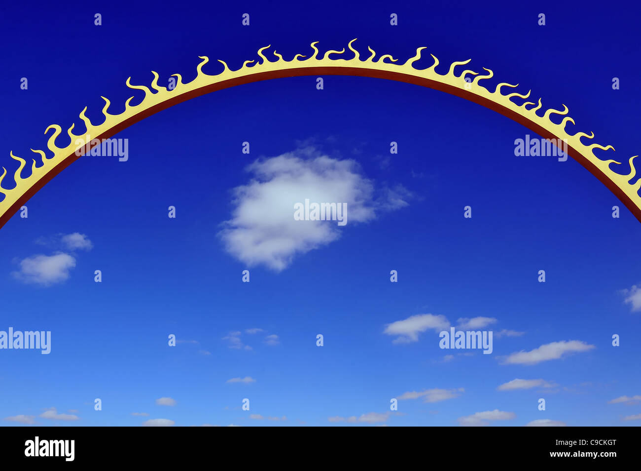 Conceptual photo of a sun with the blue sky and puffy clouds in the background - Stock Image