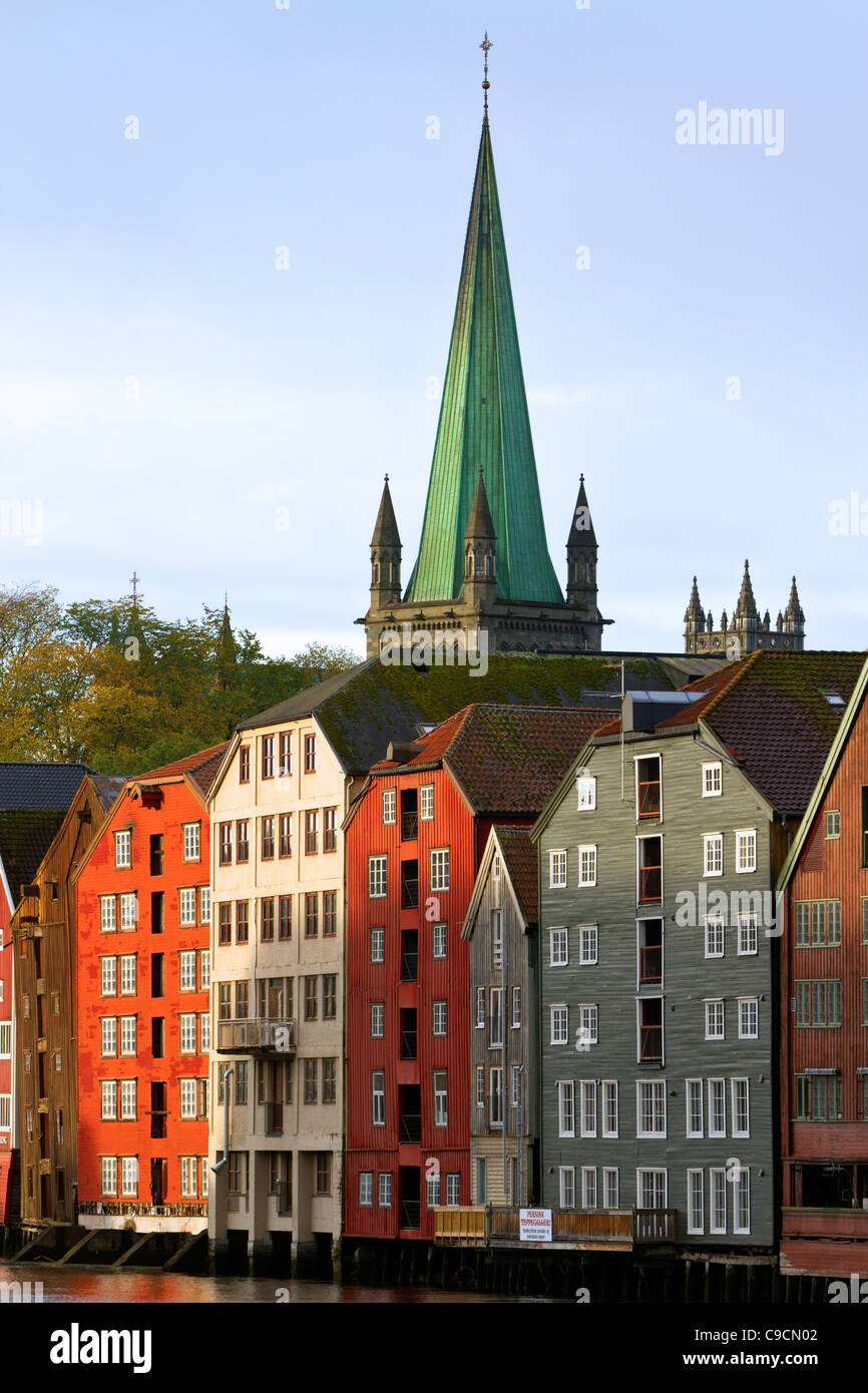 Renovated and gaily painted warehouses on Kjopmannsgata Trondheim. Nidarosdomen Cathedral spire is in the background Stock Photo