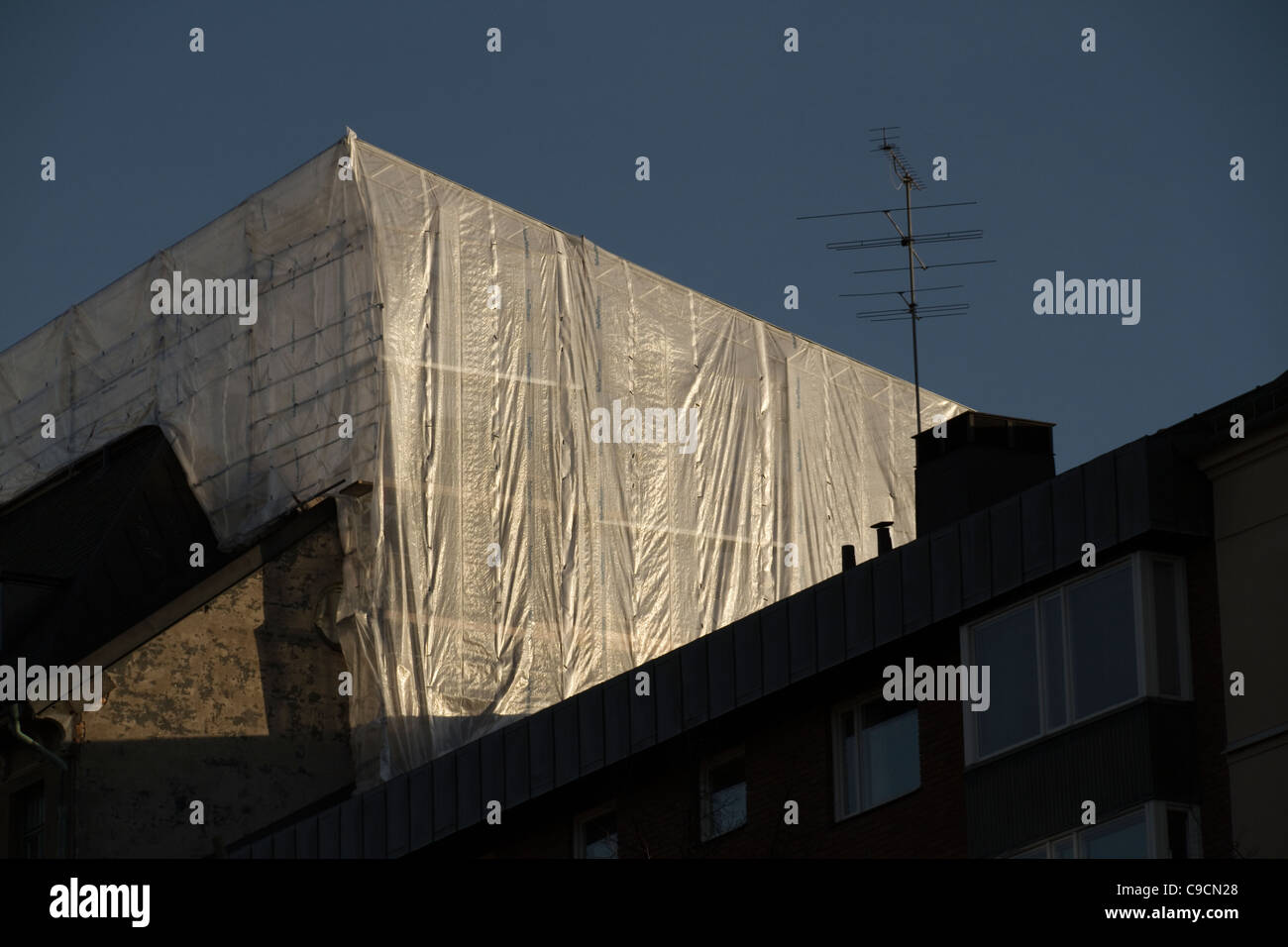 Plastic sheeting covering building at sunset - Stock Image