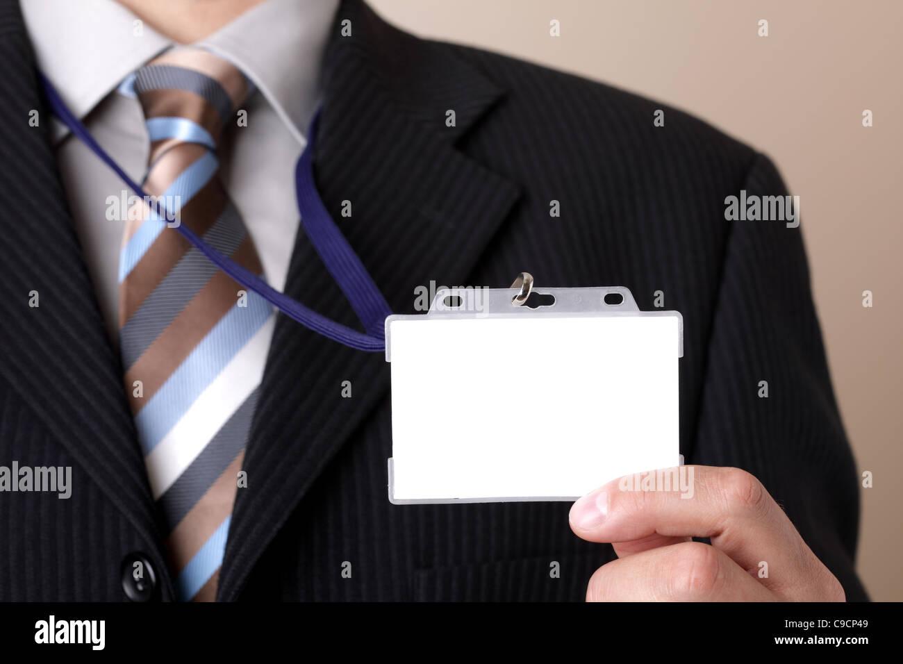 Businessman holding blank ID badge - Stock Image