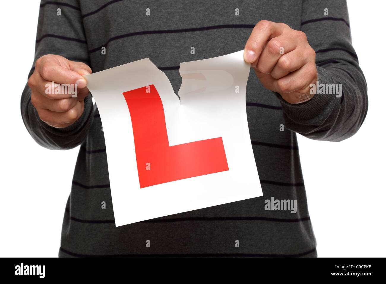 Tearing up L plate after passing driving test - Stock Image