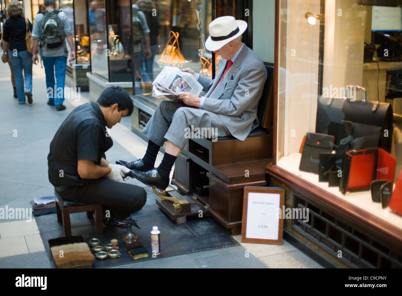A man has his shoes shined whilst he reads a newspaper in the Burlington Arcade an expensive shopping arcade. London, - Stock Image