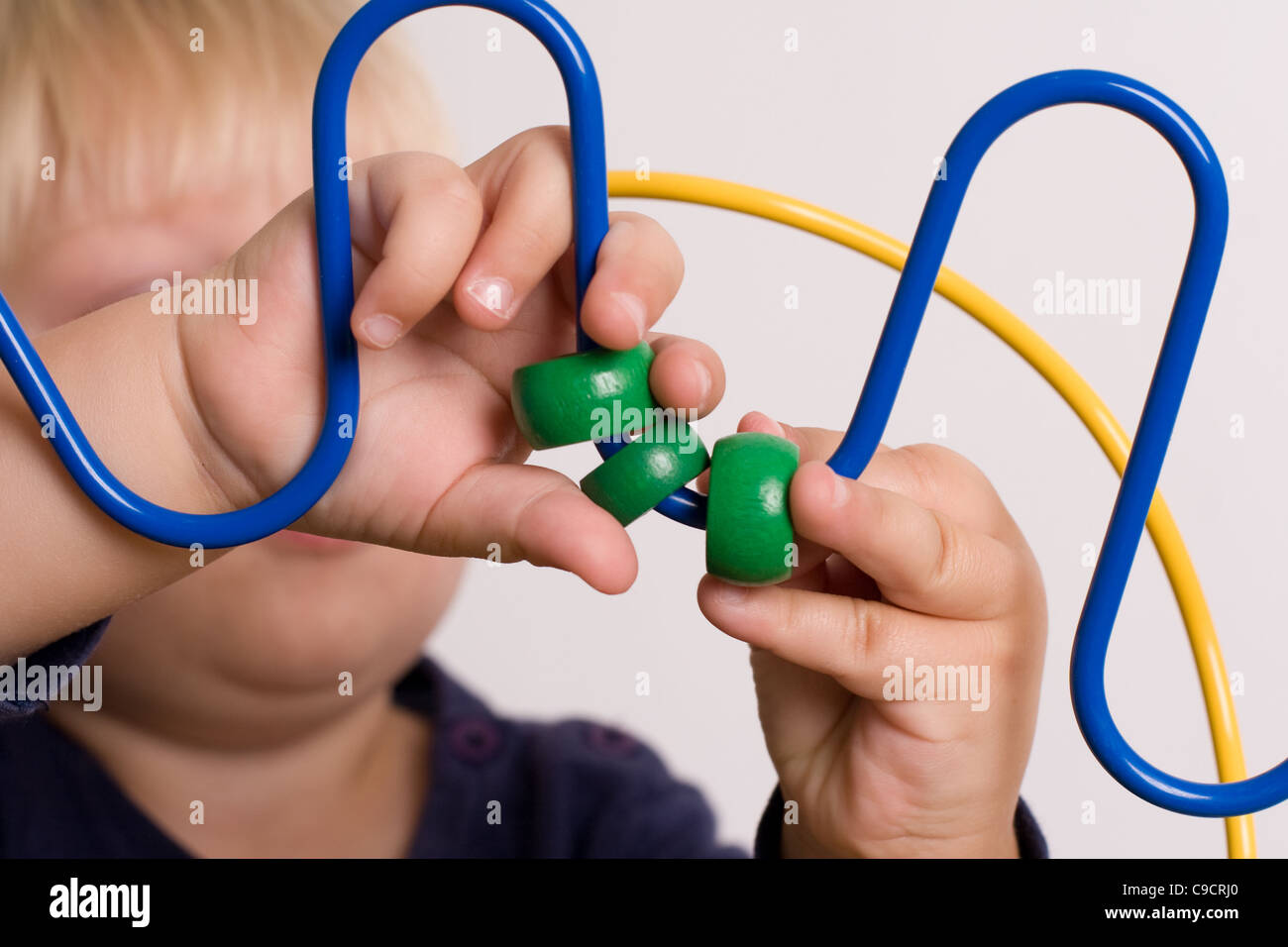 Young boy plays with the coloured beads on a play table - Stock Image
