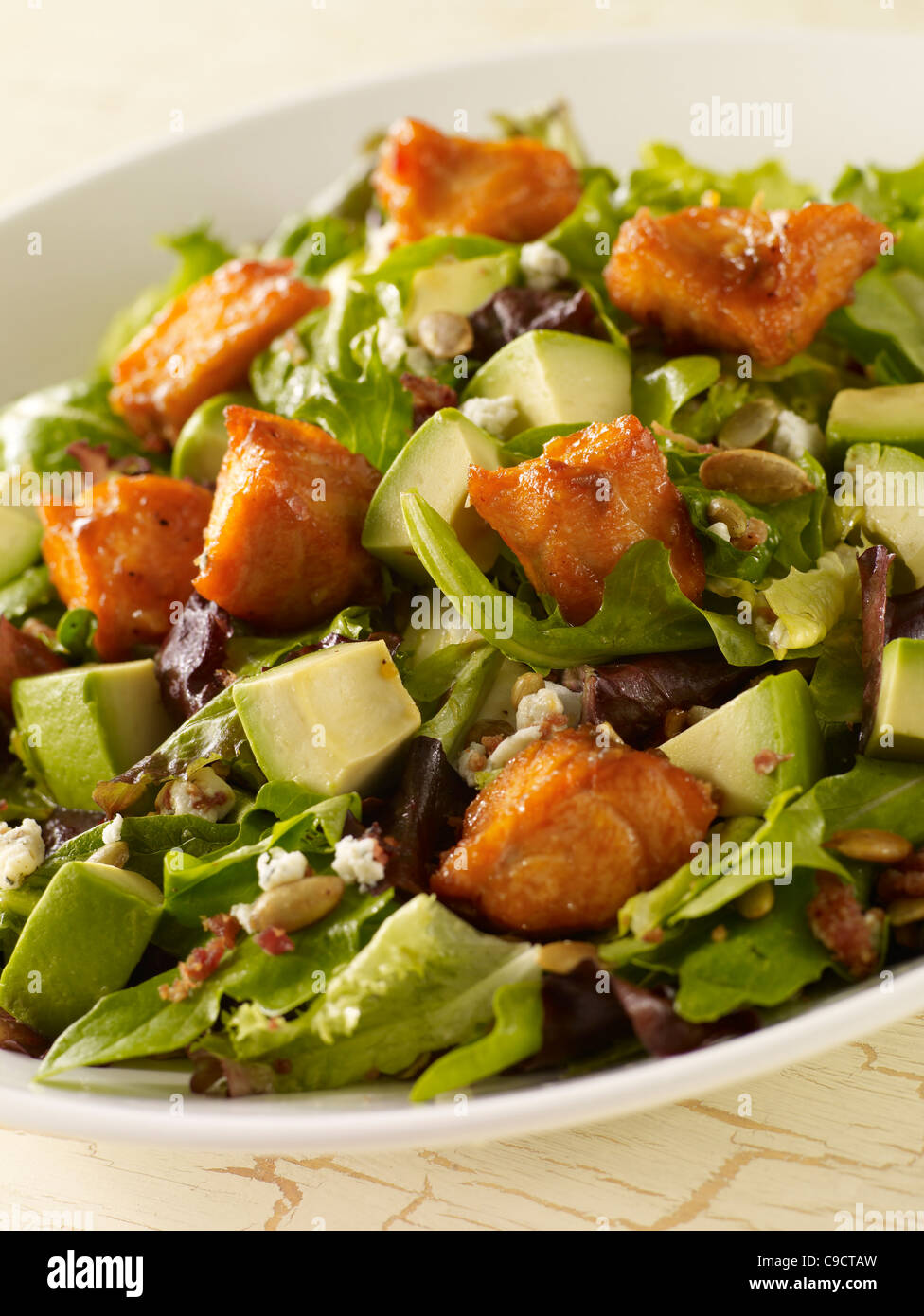 Salmon and avocado salad with leafy greens and crumbled cheese - Stock Image