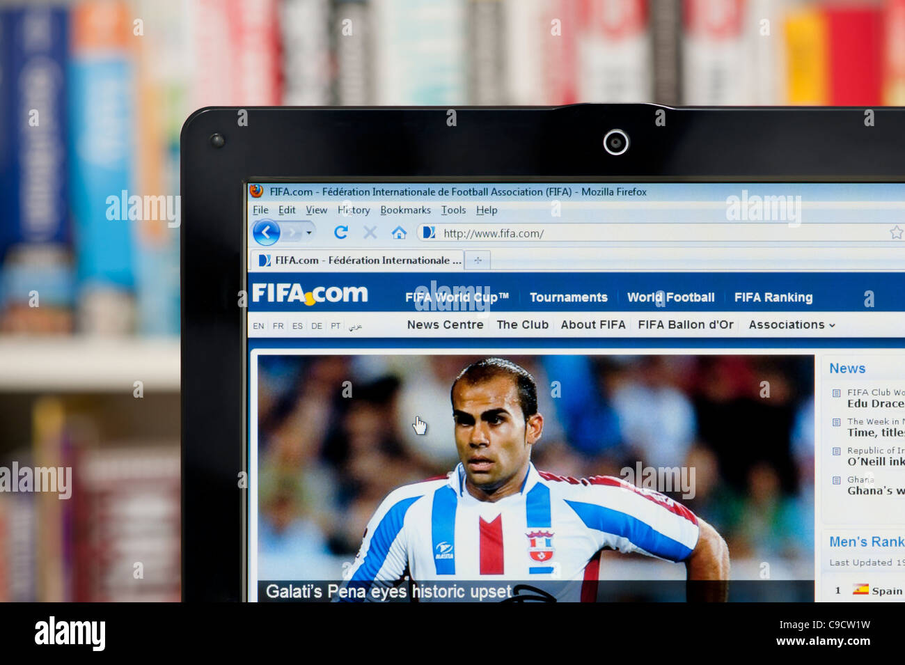 The FIFA website shot against a bookcase background (Editorial use only: print, TV, e-book and editorial website). - Stock Image