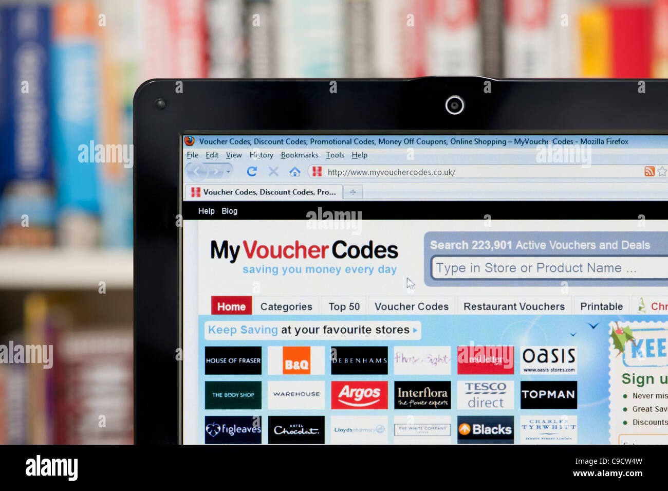 The My Voucher Codes website shot against a bookcase background (Editorial use only: ­print, TV, e-book and - Stock Image