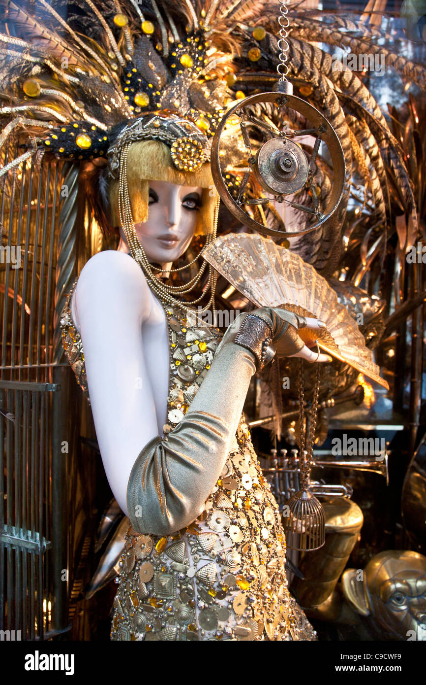 slinky siren mannequin in retro head dress with lace fan sings into very old microphone in Bergdorf Goodman Christmas - Stock Image