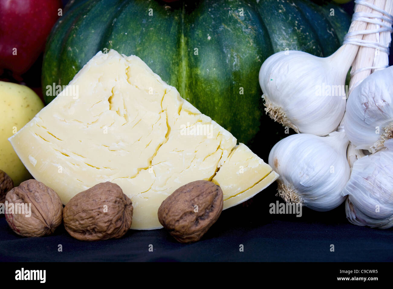 Food Ingredients - Closeup of piece of cheese with pumpkin, garlic and nuts. - Stock Image