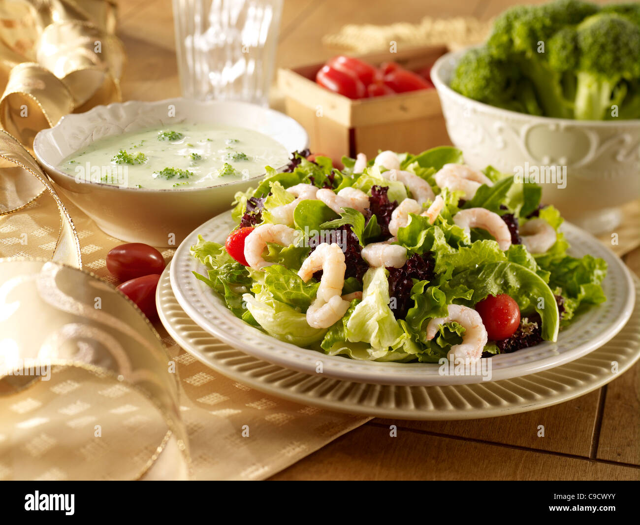 A shrimp salad and a bowl of broccoli soup in a life style holiday setting - Stock Image