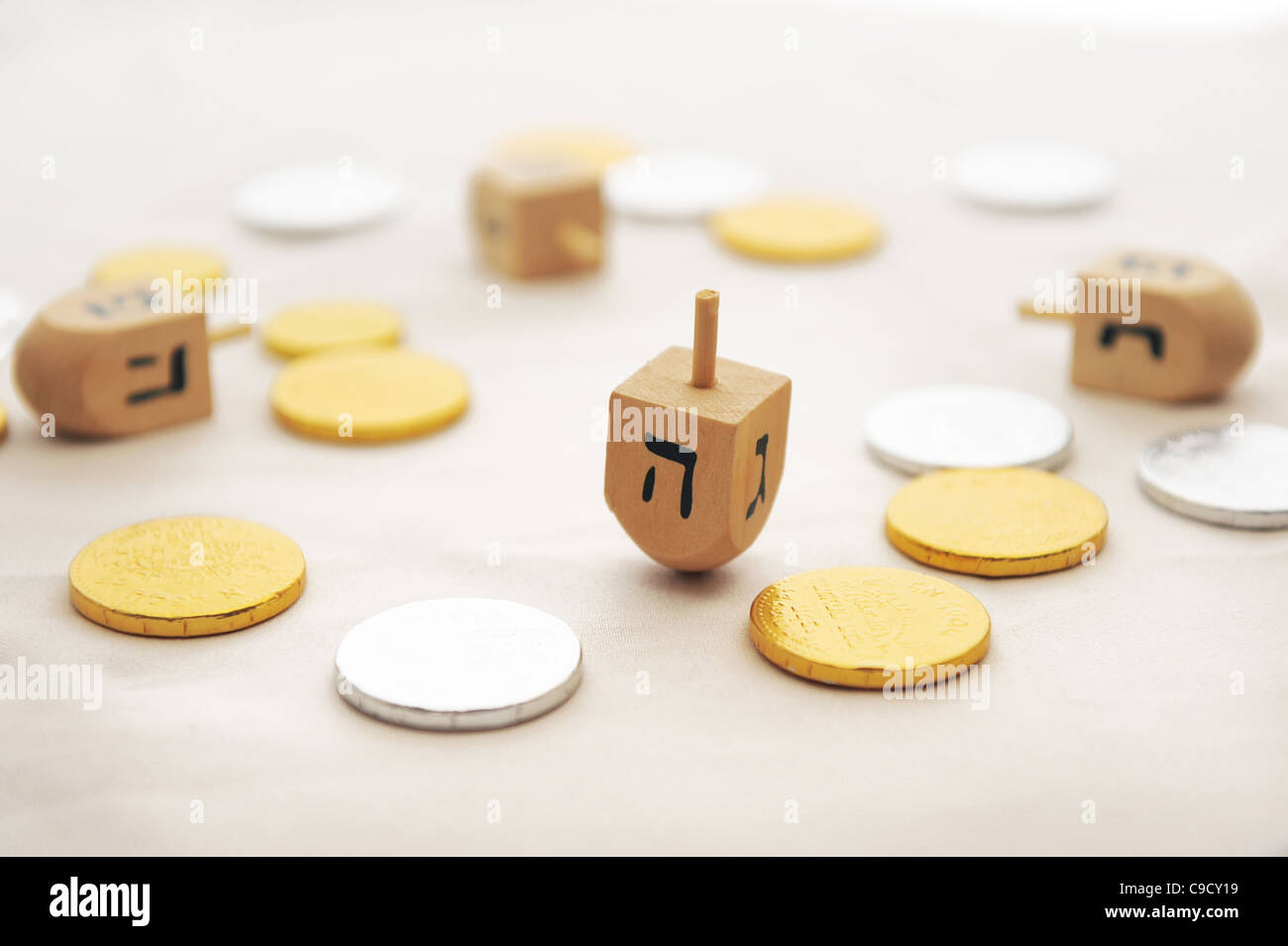 Photo of dreidels (spinng tops) and gelts (candy coins) for Hanukkah isolated on white - Stock Image