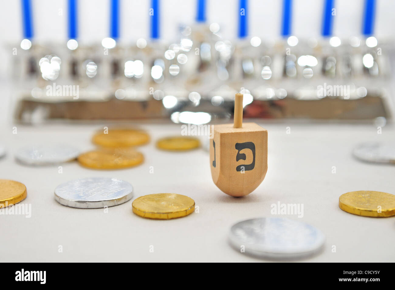 Photo of a dreidel (spinng top), gelts (candy coins) and a silver menorah for Hanukkah, isolated on white - Stock Image