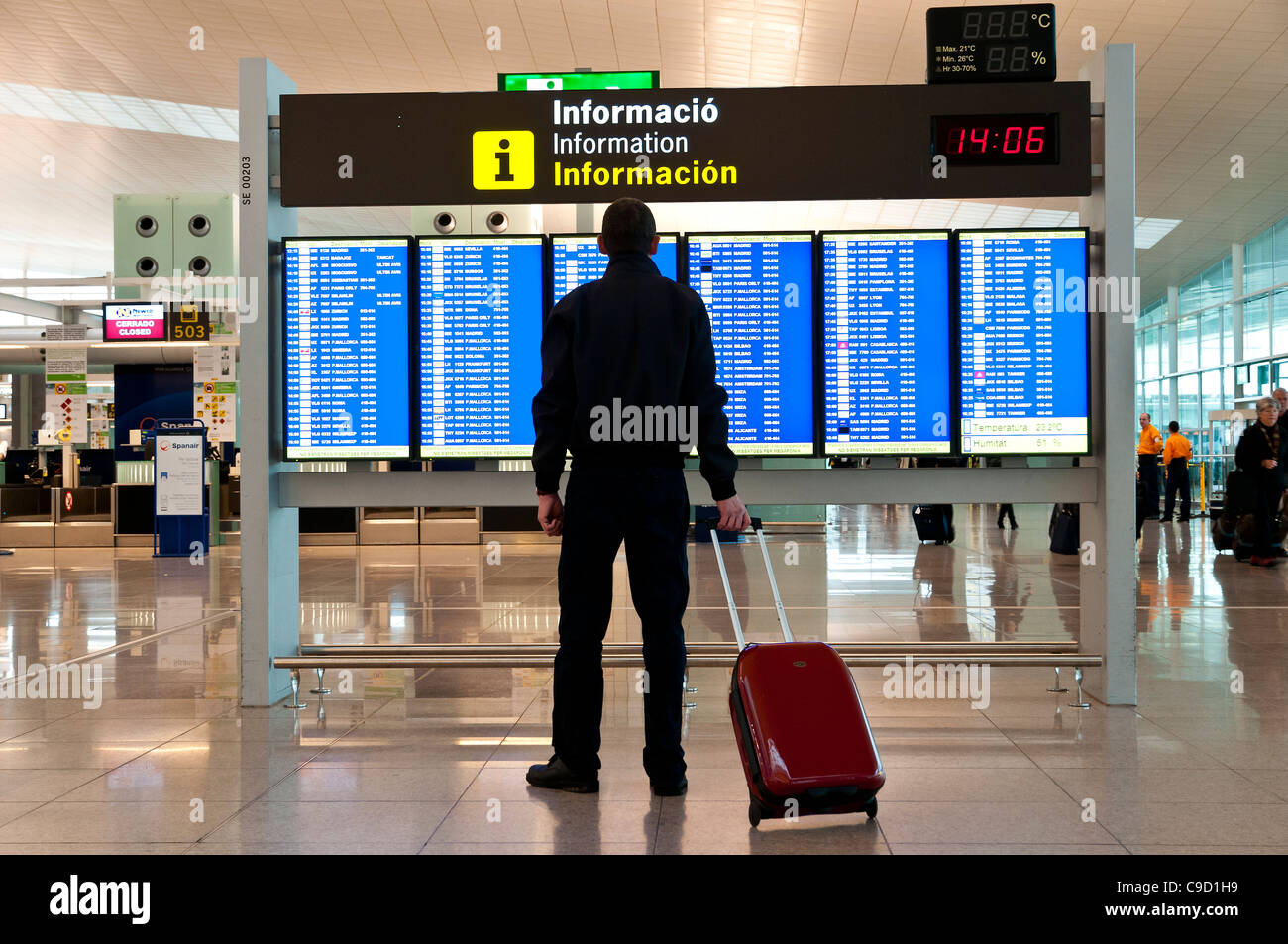 Male adult caucasian passenger with trolley watching the departures board, Barcelona El Prat international airport, - Stock Image