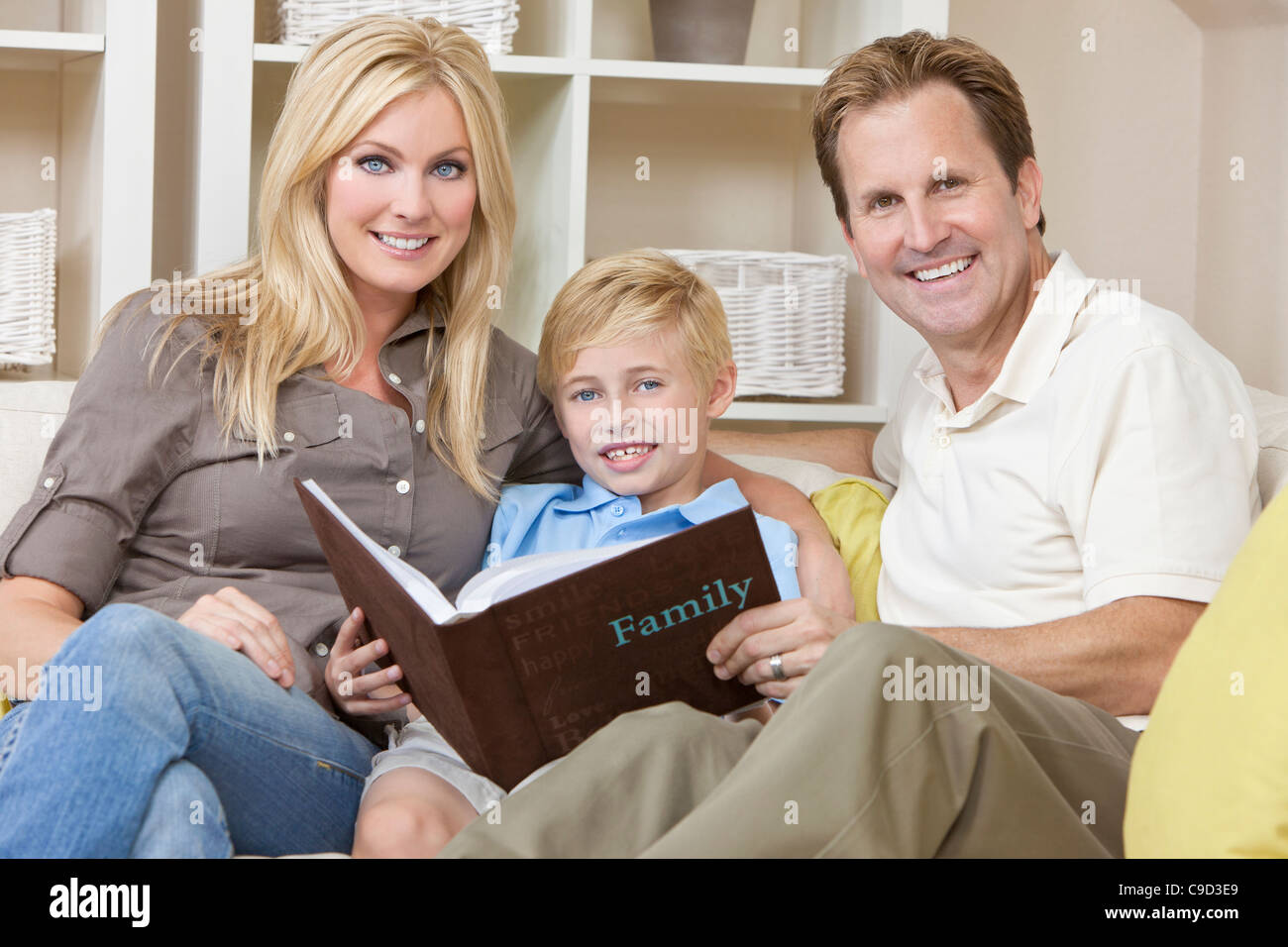 An attractive happy, young family of mother, father and son sitting on a sofa at home looking at a photo album - Stock Image