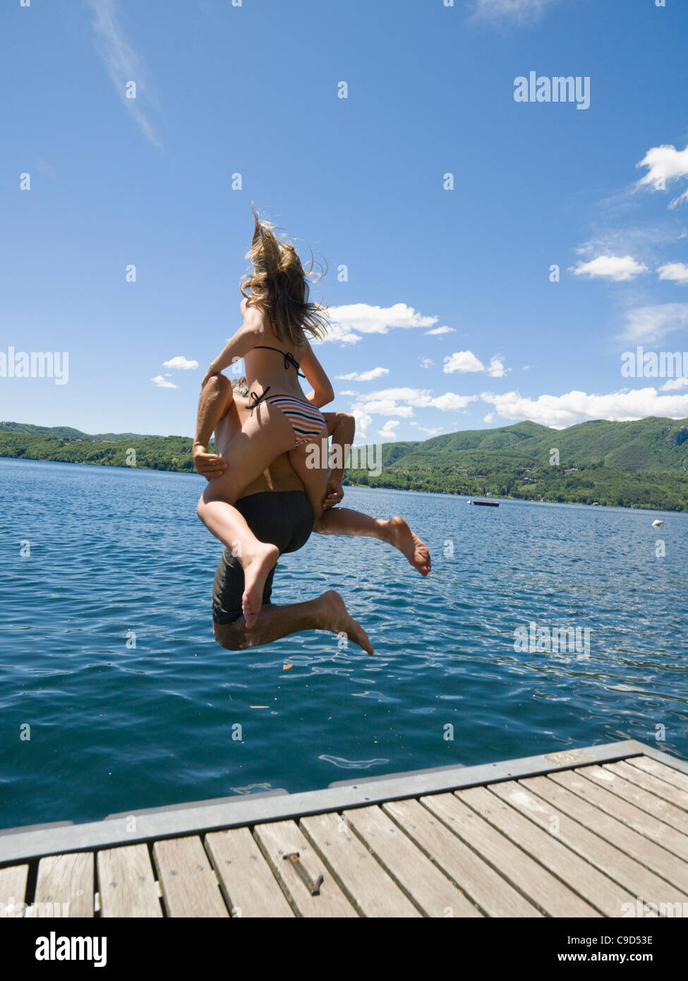 Italy, piedmont, Rear view of father and daughter (14-15) jumping off wooden wharf into Lake Orta - Stock Image