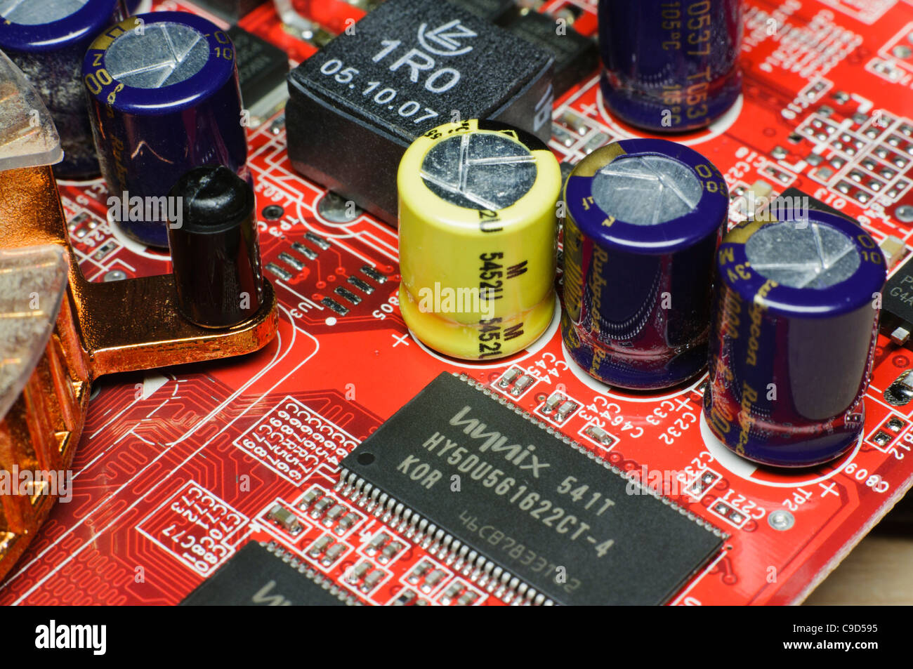 Electronic circuit board with capacitors, integrated circuits and other components. - Stock Image