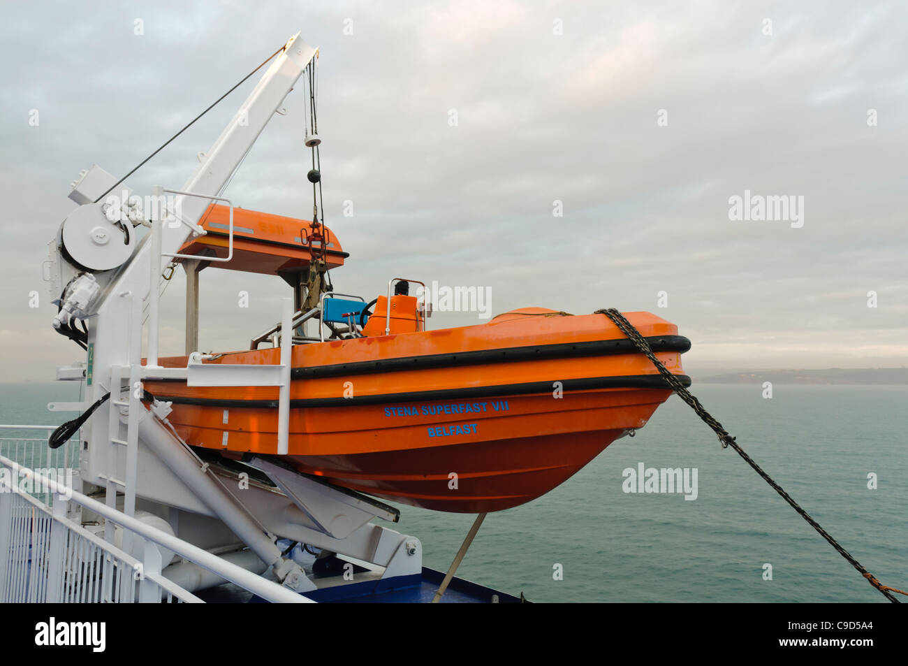 Rescue lifeboat suspended from a davit on board a large ship. Stock Photo