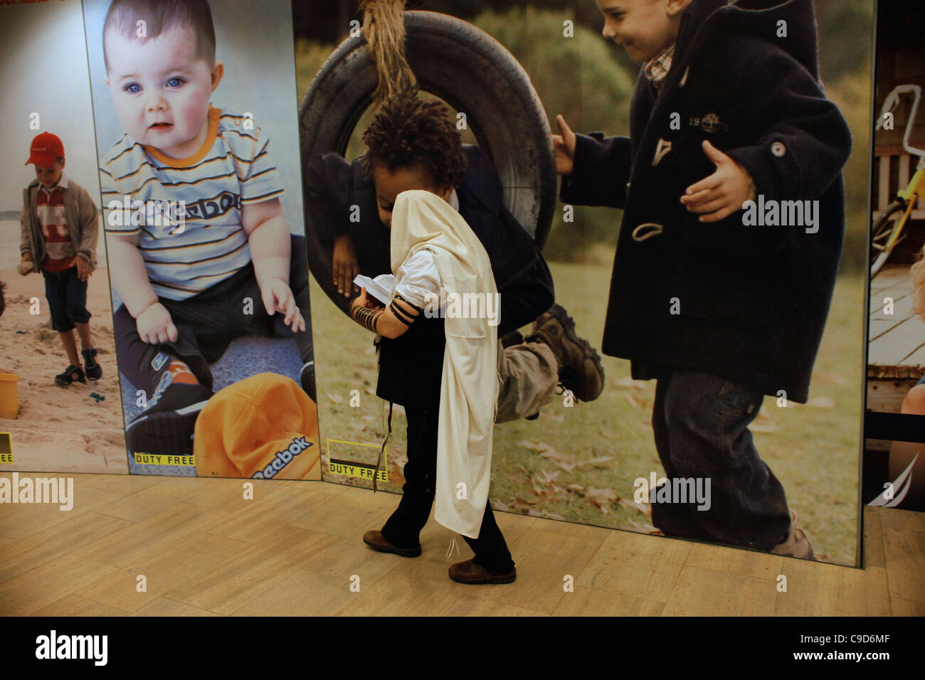 A religious Jewish man wrapped with traditional prayer shawl walk past Children clothing advertisement posters at - Stock Image