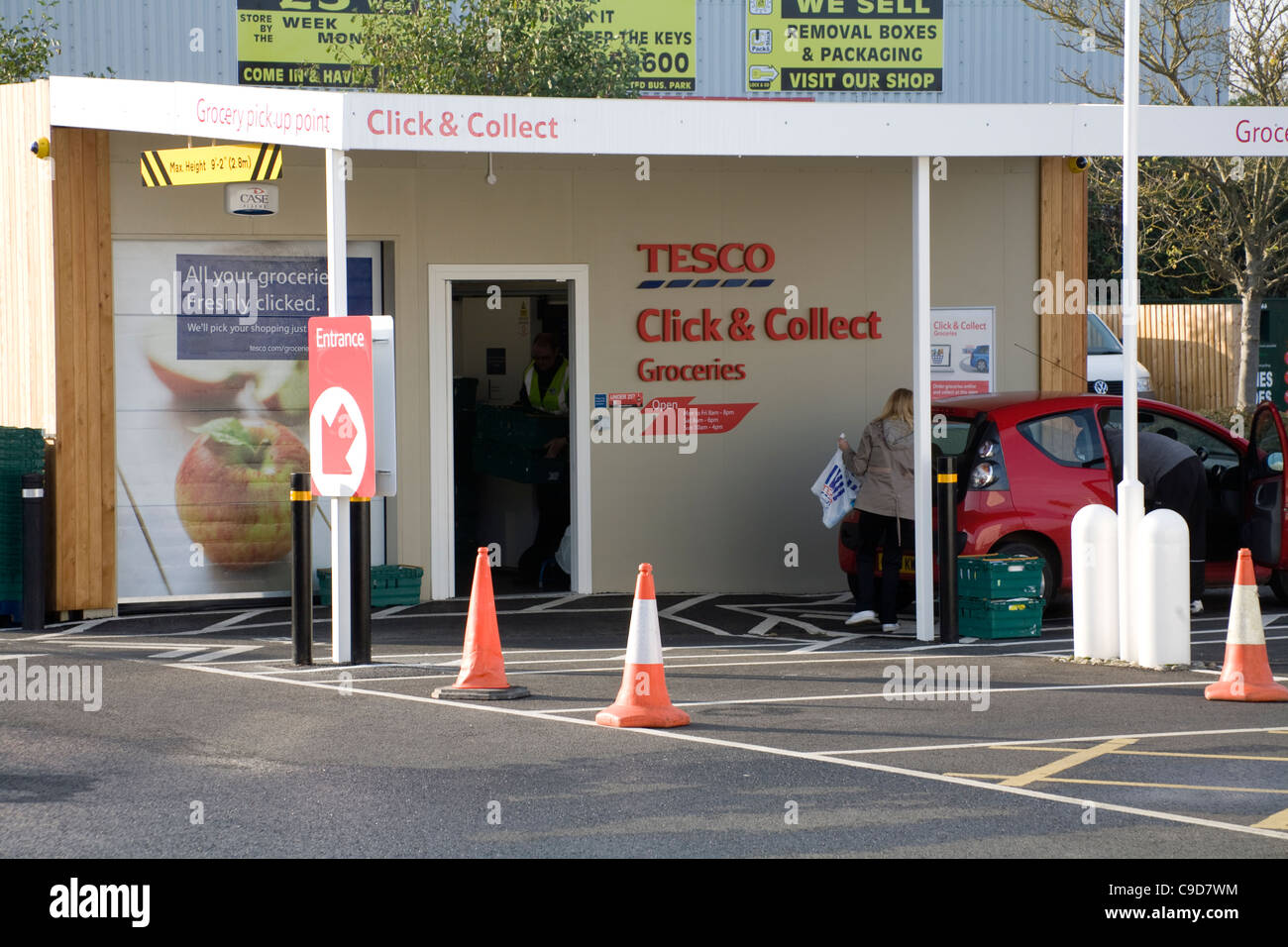 UK Blonde haired woman collecting groceries ordered online from Tesco - Stock Image
