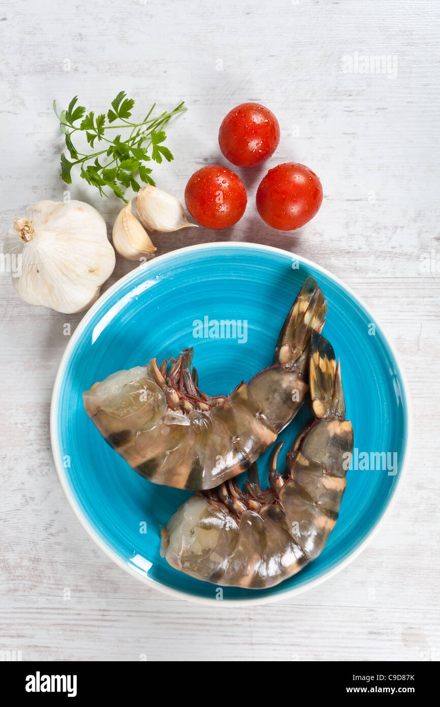 Fresh raw big prawn tails on blue plate Stock Photo