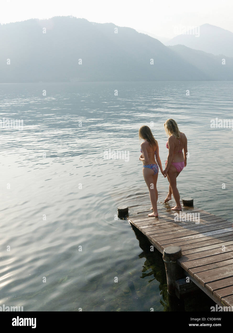 Italy, Piedmont, Lake Orta, Mother and daughter testing water at lake edge - Stock Image