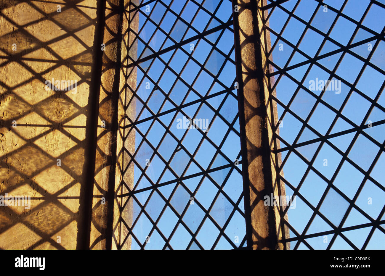 United Kingdom, Norfolk, Detail of diamond-leaded window set in carved sandstone and casting shadows of flawed handmade - Stock Image