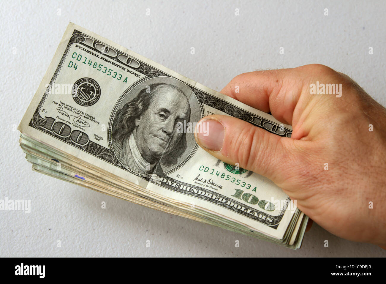 Man's hand holding stack of US money with 100 dollar bill on top - Stock Image