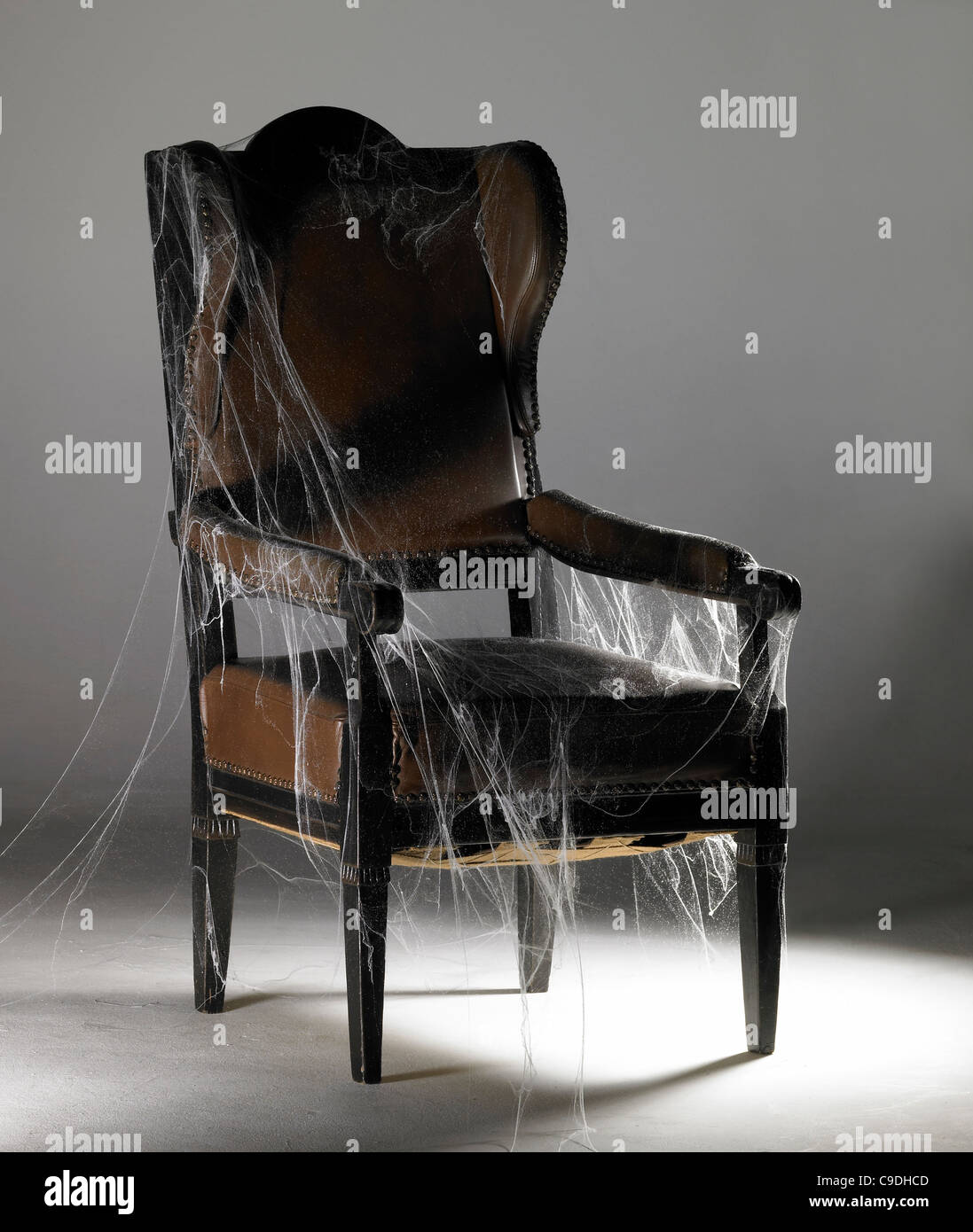 studio photography of a old nostalgic wing chair covered with artificial cobwebs in illuminated grey back - Stock Image