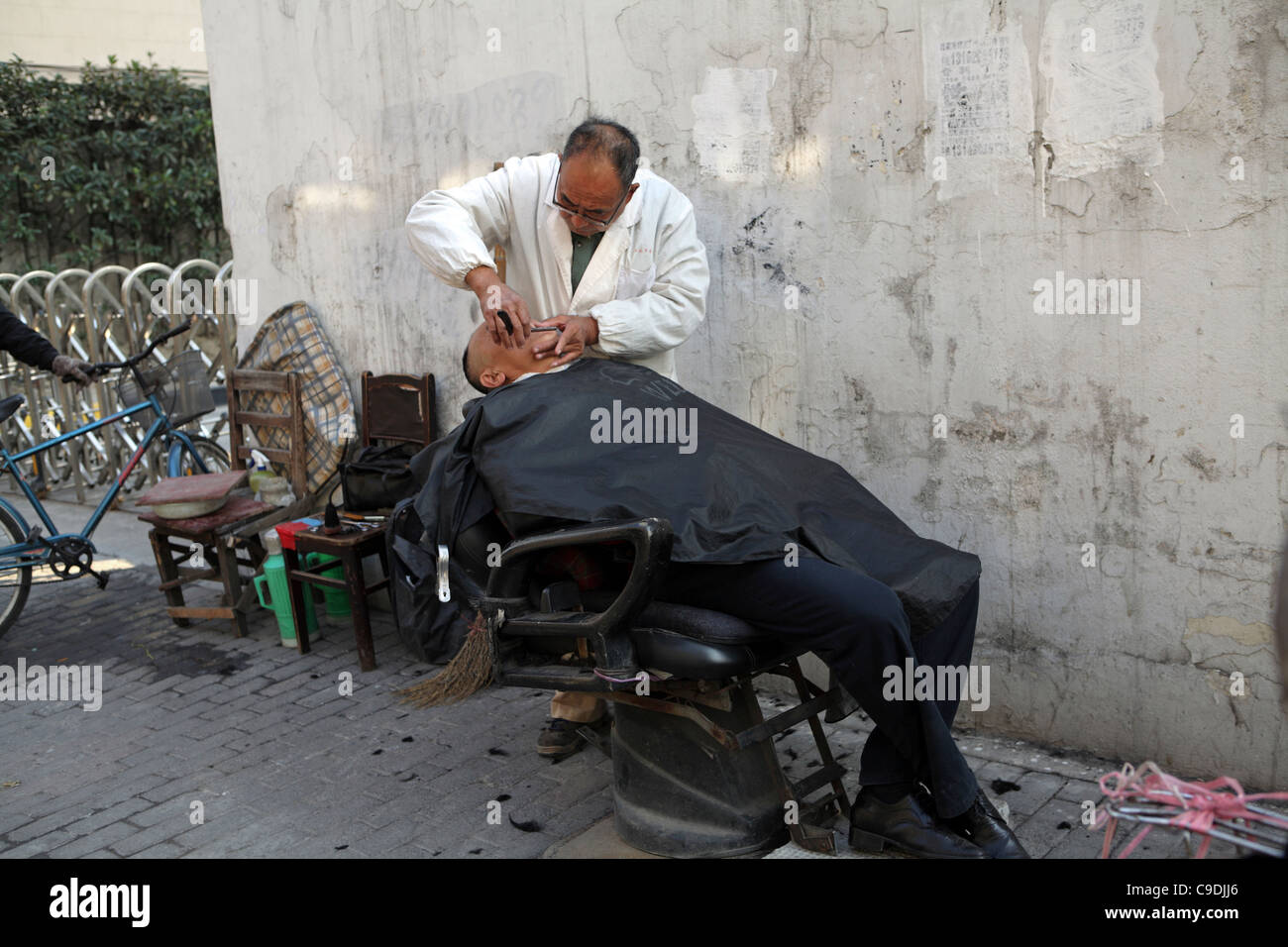 Barber giving client a shave outside on pavement, street market Shanghai, China, Asia - Stock Image