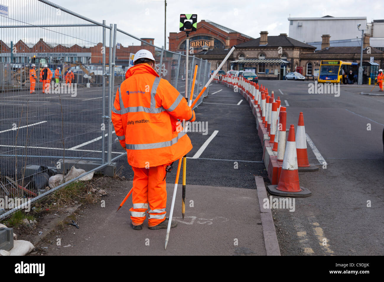 Building surveyor in a Hi-Viz jacket and trousers taking levels. Stock Photo