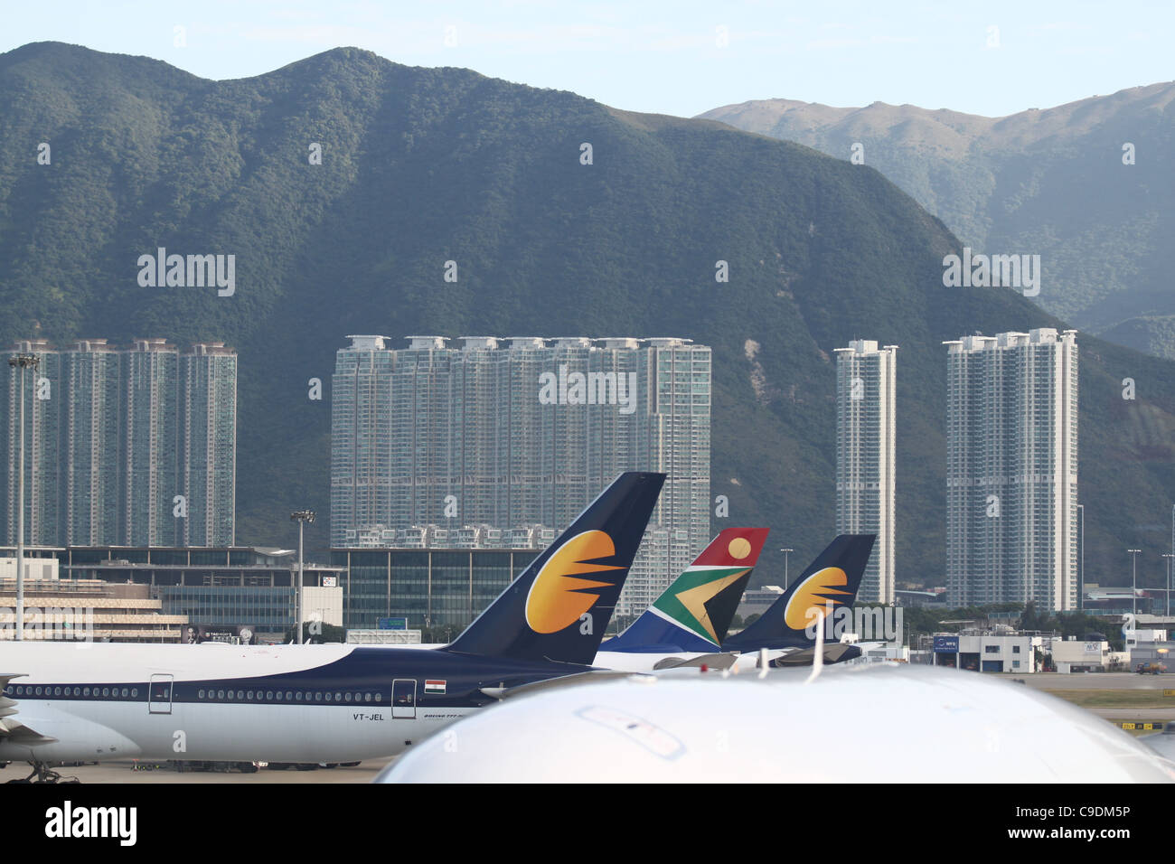 Airplane tails and high rise buildings at the Hong Kong Airport Stock Photo