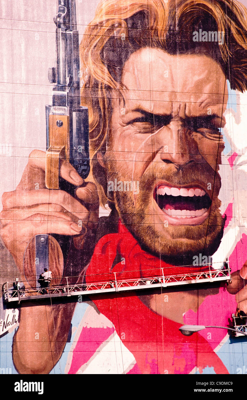 workers post giant billboard of Clint Eastwood on building on Sunset Boulevard Hollywood Los Angeles Southern California - Stock Image