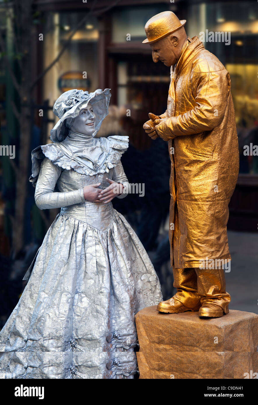 Gold man with Silver lady street performer chatting at Covent Garden in London UK - Stock Image