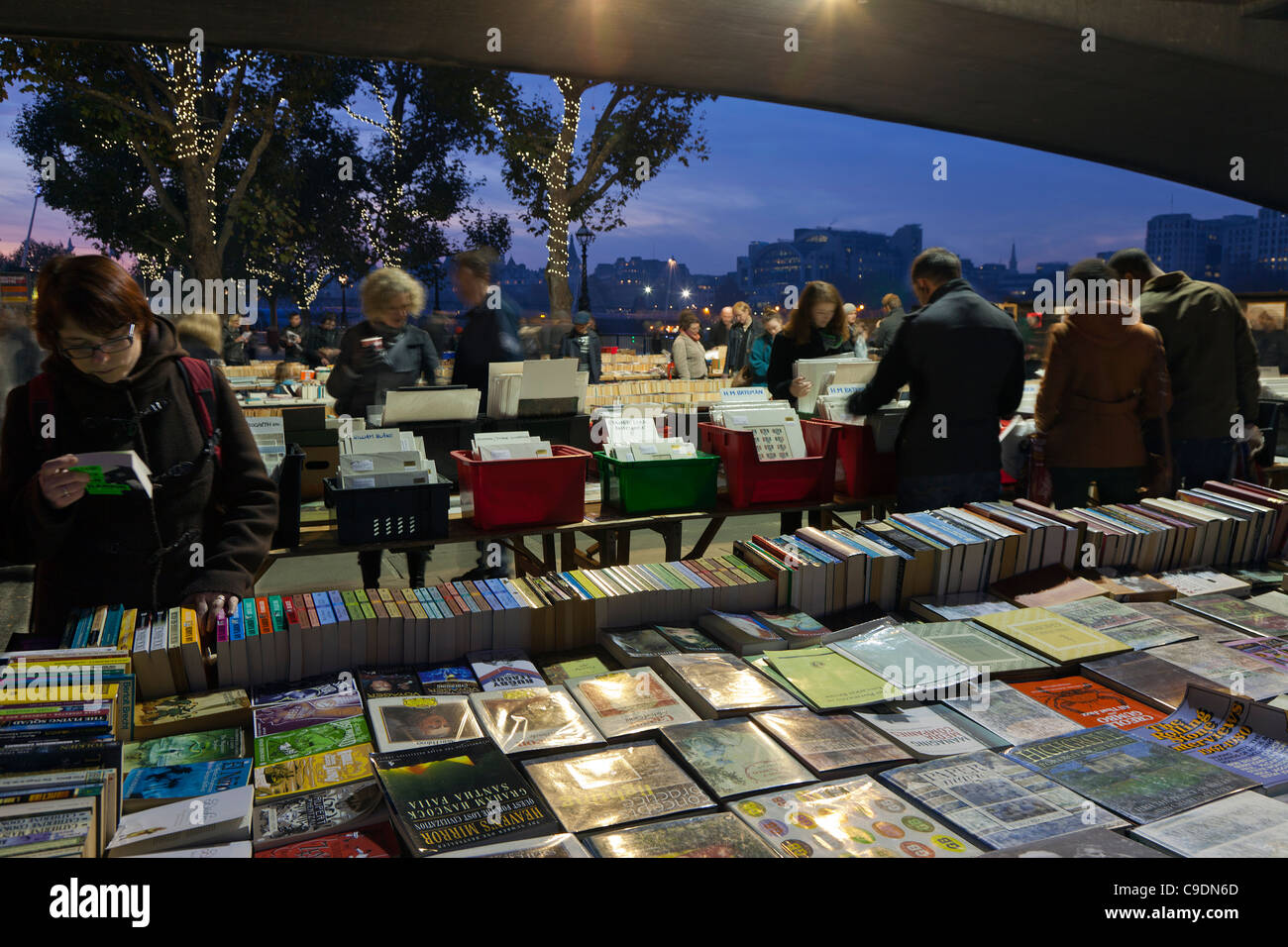 The open air secondhand book sales on the South Bank London before Christmas at dusk Stock Photo