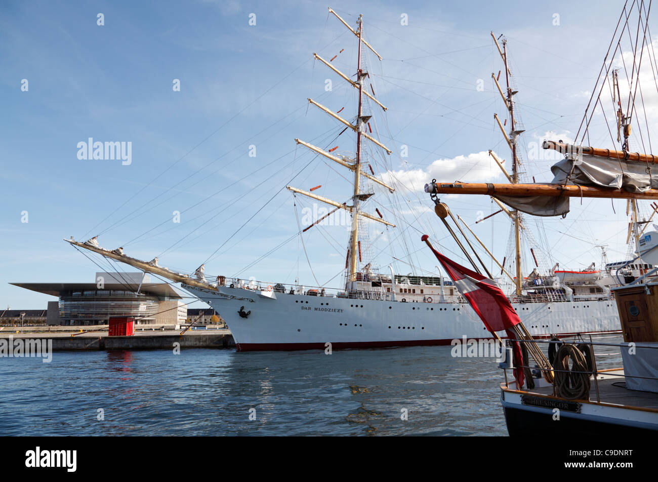 The large Polish tall ship Dar Mlodziezy moored near The Opera House on a visit to Copenhagen, Dannebrog on Danish - Stock Image