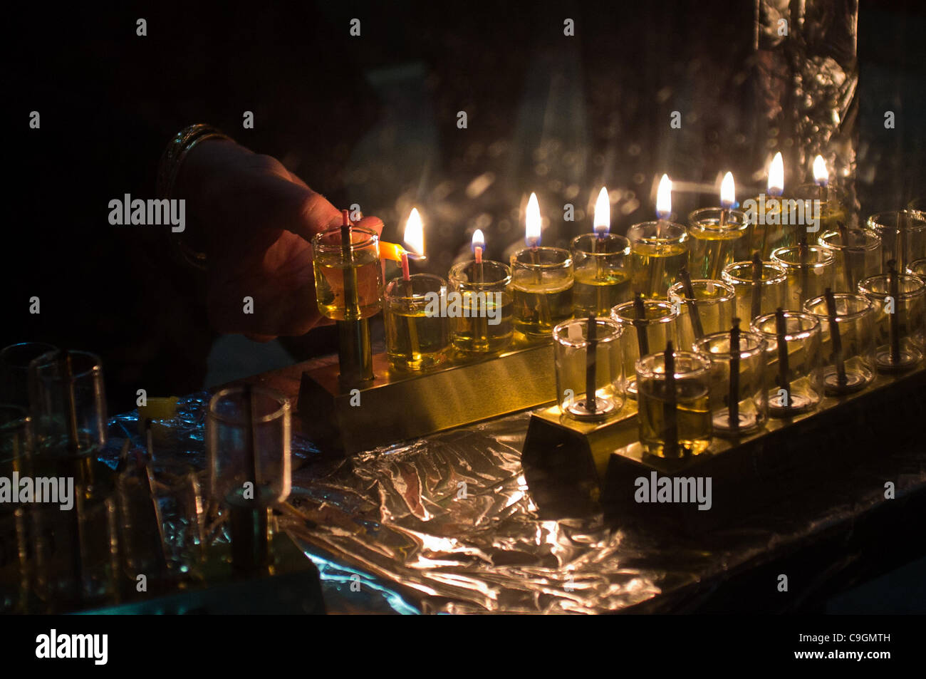 Young ladies light a chanukkiah, an eight-branched menorah, on the eight and last night of the holiday of Chanukah. - Stock Image