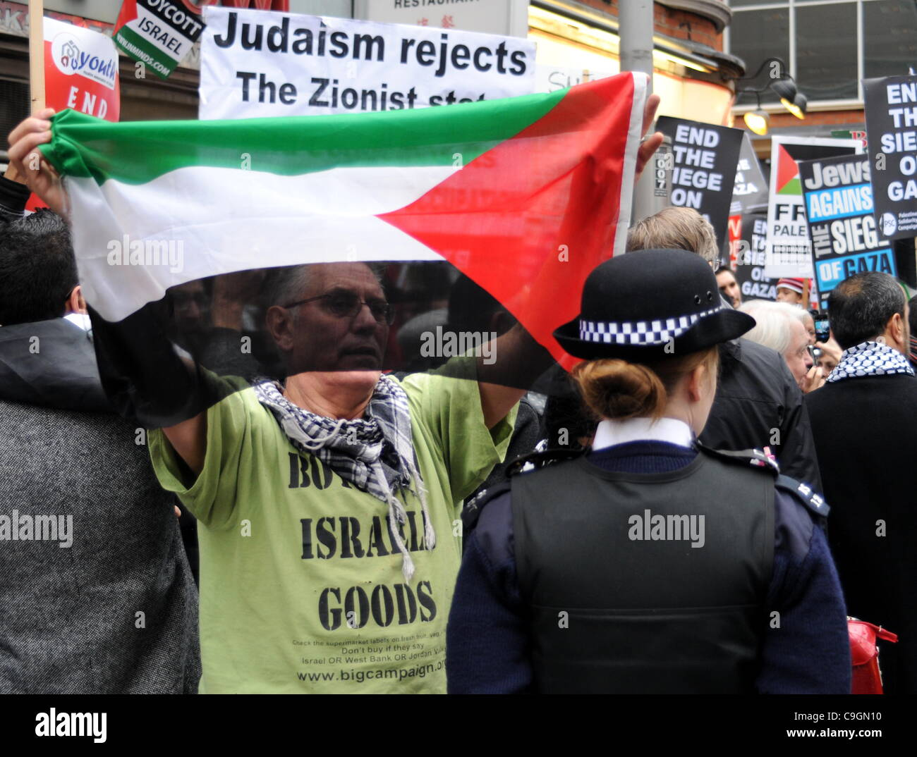 Protester holds up a Palestinian flag to a WPC during the Stop the War Coalition's demonstration outside the Israeli - Stock Image