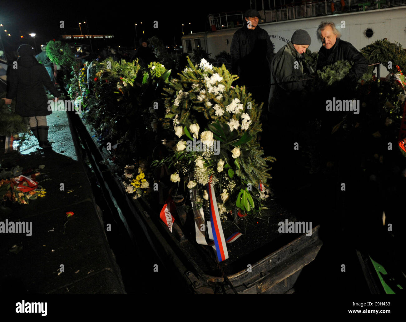 Volunteers collect the flowers that people brought to the coffin of former Czech president Vaclav Havel in Prague - Stock Image