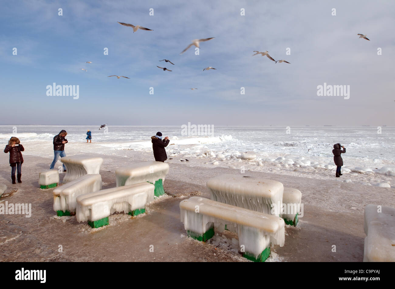 Icy cafe tables and benches on the beach of the frozen Black Sea, a rare phenomenon, last time it occured in 1977, Stock Photo