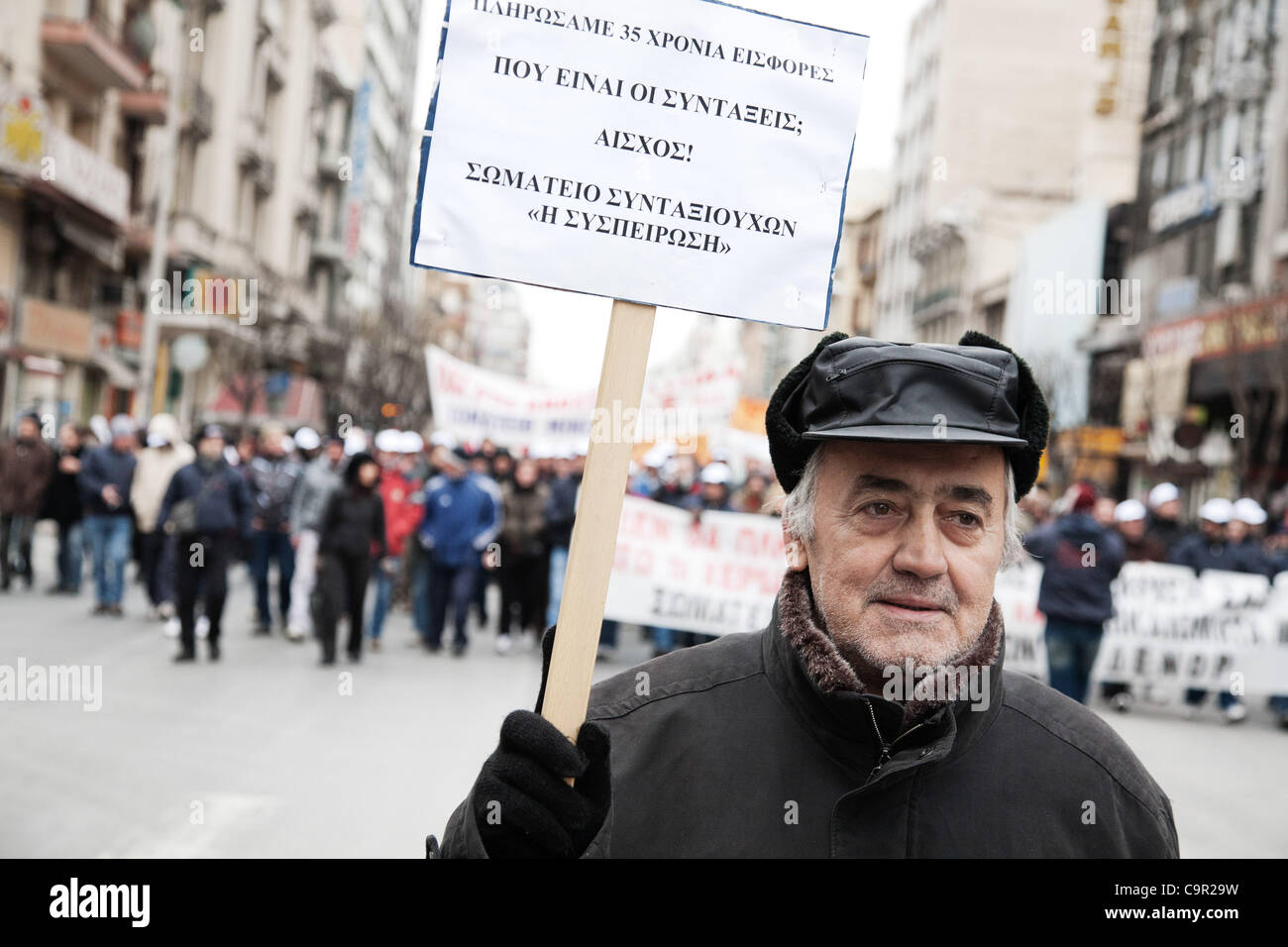 Greek elderly protester carry a placard against the new austerity measures. 48-hour nationwide strike. Protests - Stock Image