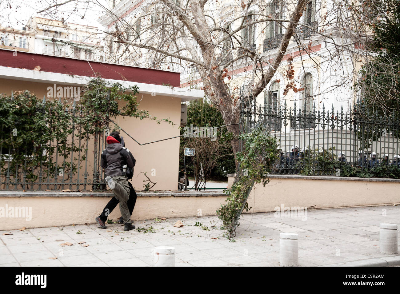 A protester throws a stone at police during the strike. 48-hour nationwide strike. Protests in Thessaloniki against - Stock Image