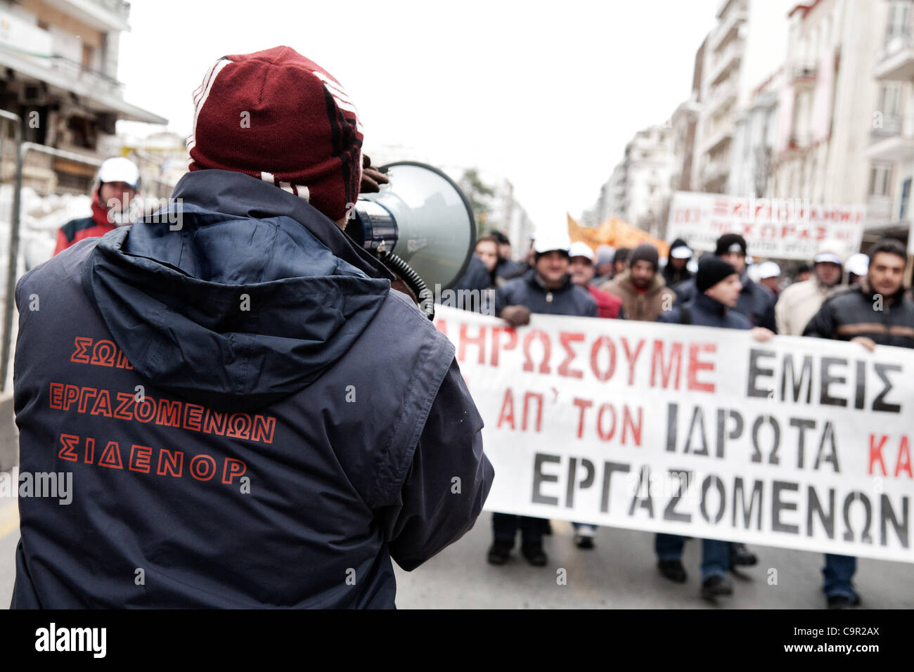 Greek protesters, employees of the steel production company Sidenor, carry a banner against the new austerity measures. - Stock Image