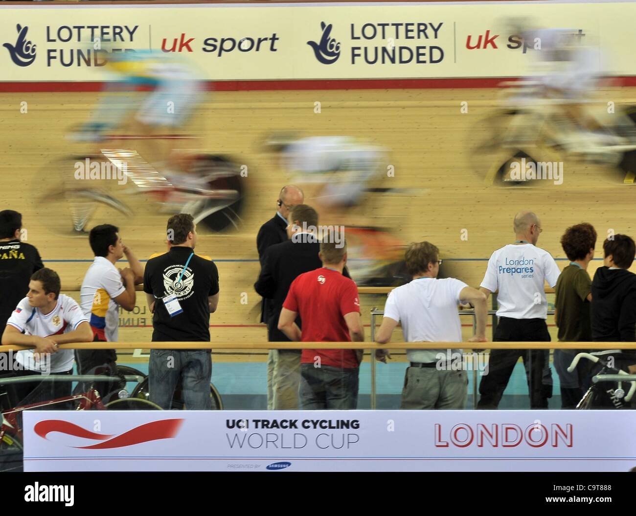 OLYMPIC 2012 VELODROME, LONDON, UK, Friday  17/02/2012. Riders go past the UCI Track Cycling World Cup London sign. - Stock Image