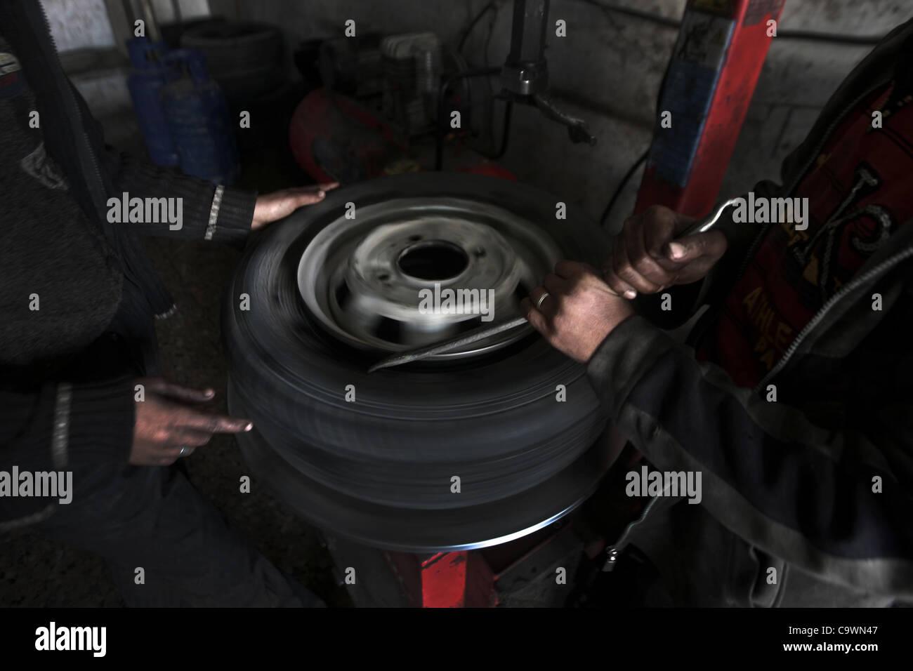 Feb. 23, 2012 - Gaza City, Gaza Strip, Palestinian Territory - Palestinian children work repairing a car tyre in - Stock Image