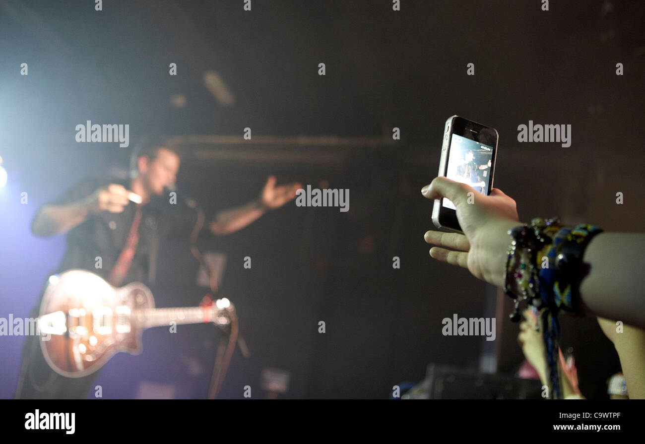 woman uses iphone to video from the  front row at theTyler Ward gig at the Speakeasy Queens University Belfast Students - Stock Image