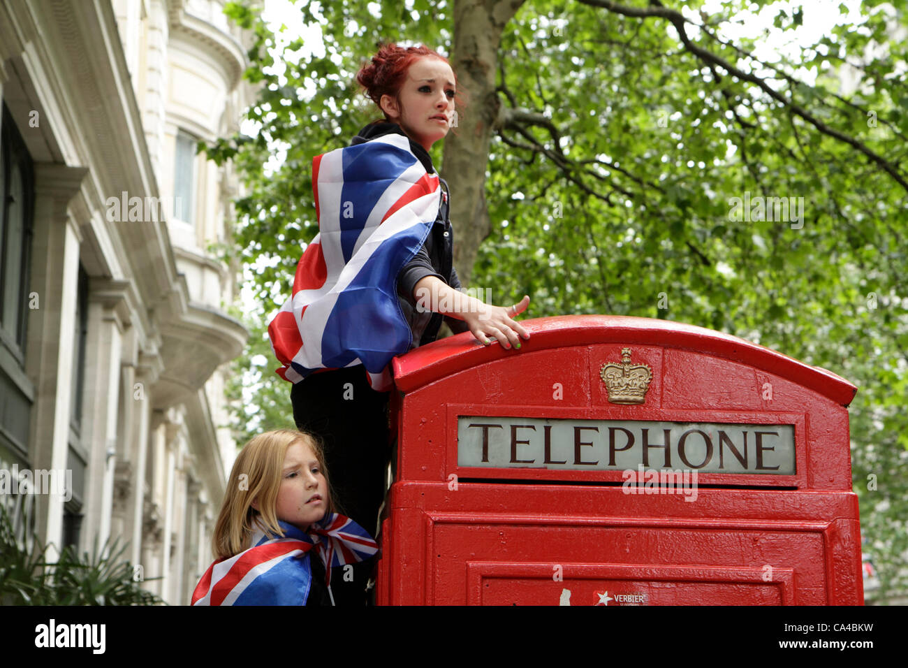 Two girls climb onto a telephone box to watch the Queen's Diamond Jubilee carriage procession, London - Stock Image